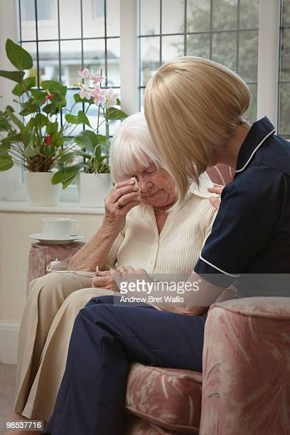 Carer supporting an upset elderly woman at home