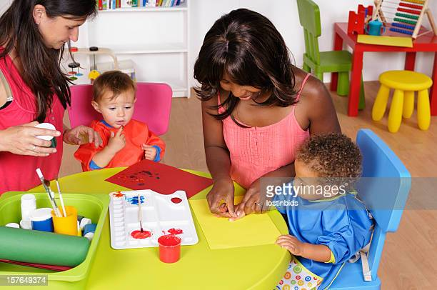 Carers And Babies/ Toddlers Doing Finger Painting
