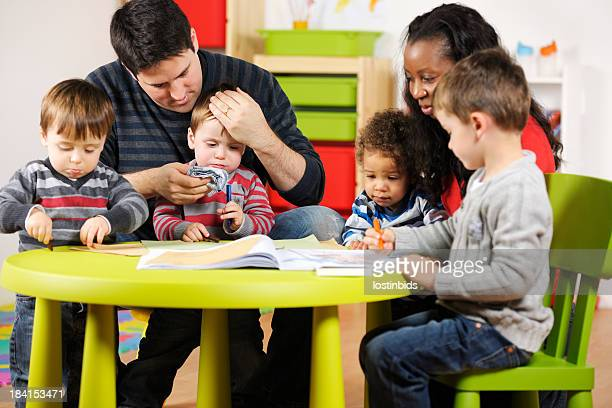 Carers Supervising Group Of Toddlers And Little Boy
