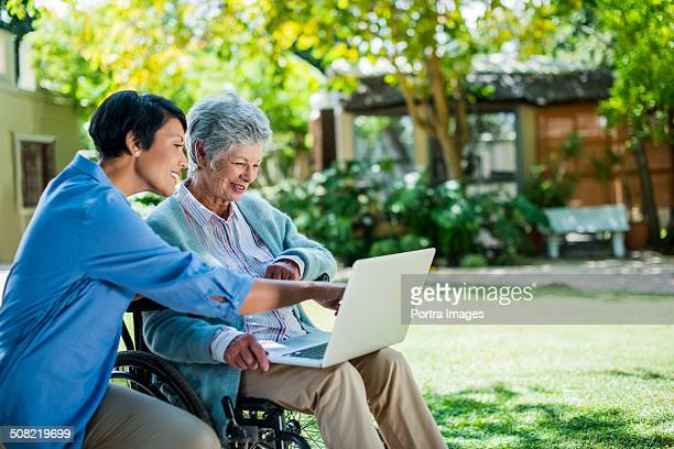 caretaker and disabled senior woman using laptop - retirement community stock pictures, royalty-free photos & images