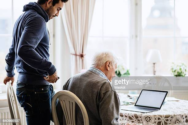Caretaker and senior male using laptop at dinning table