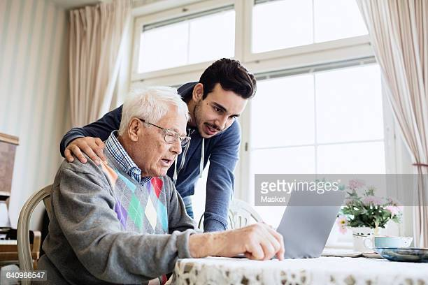 Caretaker and senior man using laptop in nursing home