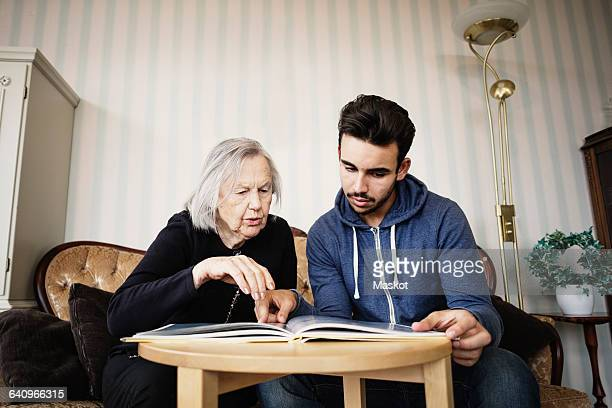Caretaker and senior woman discussing while reading book at nursing home