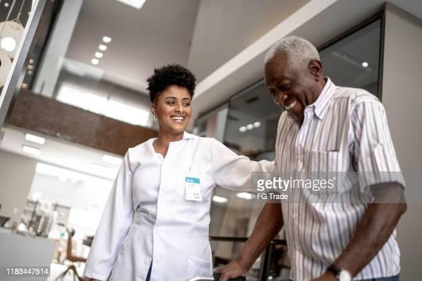 caretaker assisteren senior man met walker - medicare stockfoto's en -beelden
