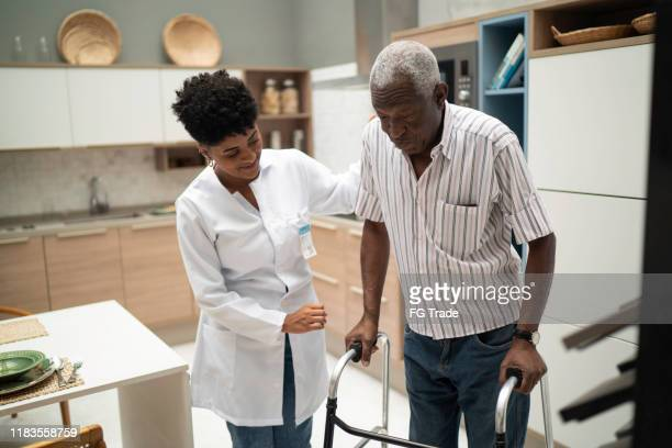 caretaker assisting senior man with walker - patience stock pictures, royalty-free photos & images