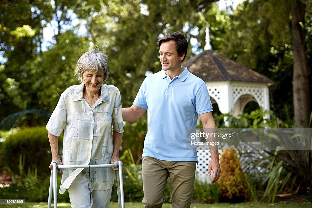 Caretaker assisting senior woman in using walker : Stock Photo
