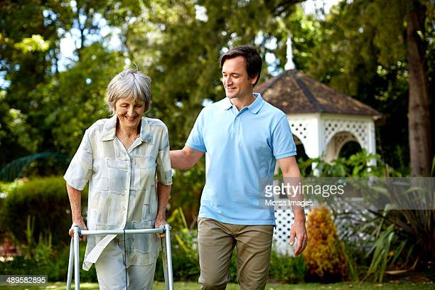 caretaker assisting senior woman in using walker - janitor stock photos and pictures