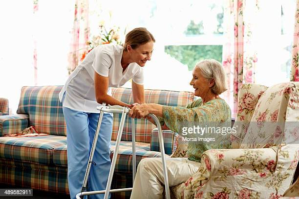 caretaker assisting senior woman with walker - janitor stock photos and pictures