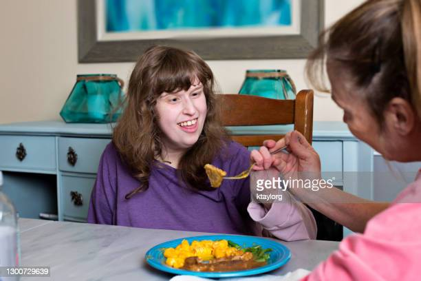 caretaker assists disabled young adult eating her dinner - autism stock pictures, royalty-free photos & images