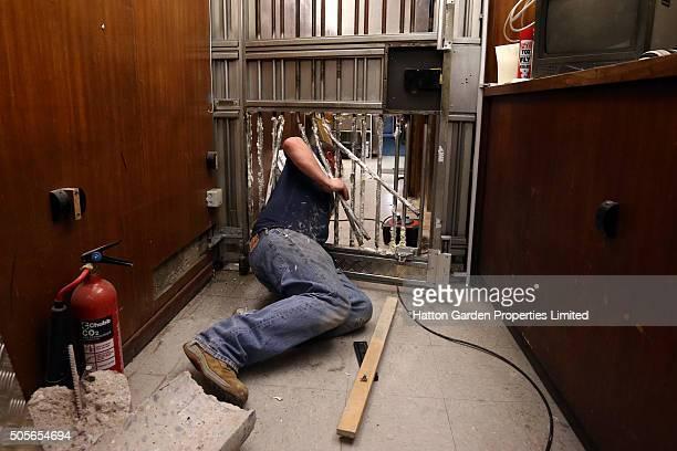 Caretaker climbs through the bars of a reinforced door that was broken through to access the underground vault of the Hatton Garden Safe Deposit...
