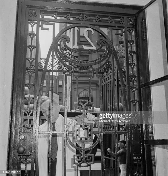 A caretaker closing the gate of the 21 Club restaurant and speakeasy on West 52nd Street in New York City US September 1945