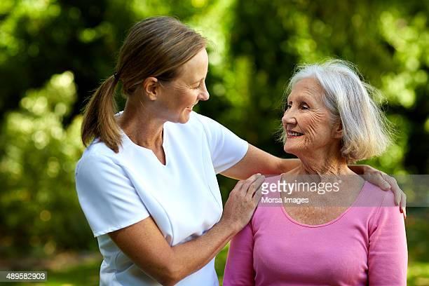caretaker consoling senior woman in park - hand auf der schulter stock-fotos und bilder