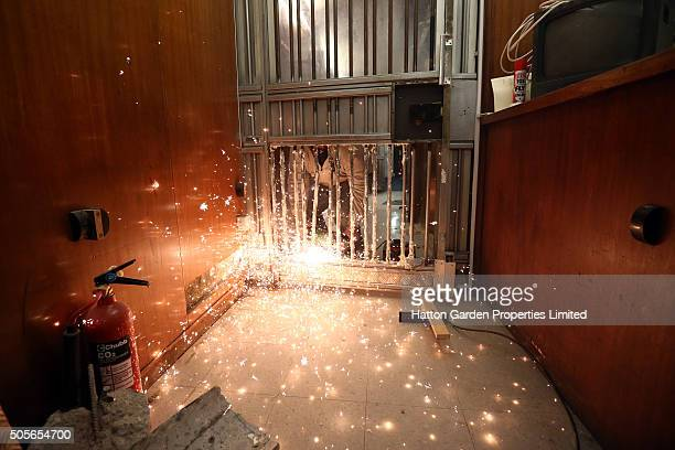 Caretaker cuts through the bars of a reinforced door that was broken through to access the underground vault of the Hatton Garden Safe Deposit...