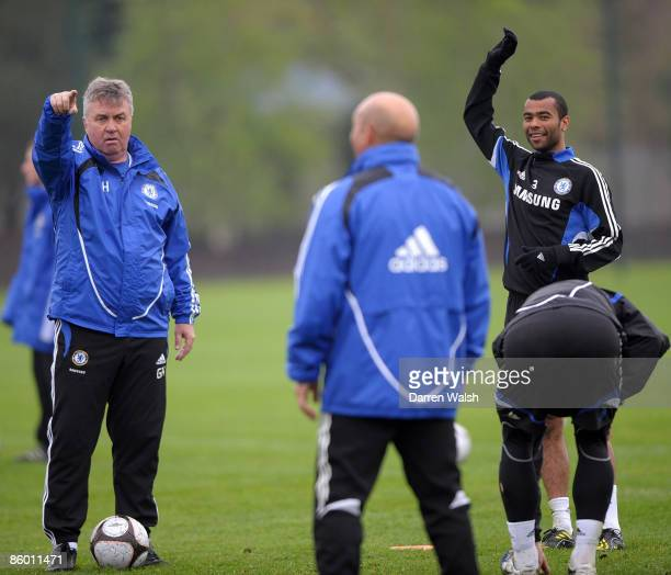 Caretaker first team coach Guus Hiddink gives instructions as Ashley Cole of Chelsea smiles during the Chelsea training session at the Chelsea...