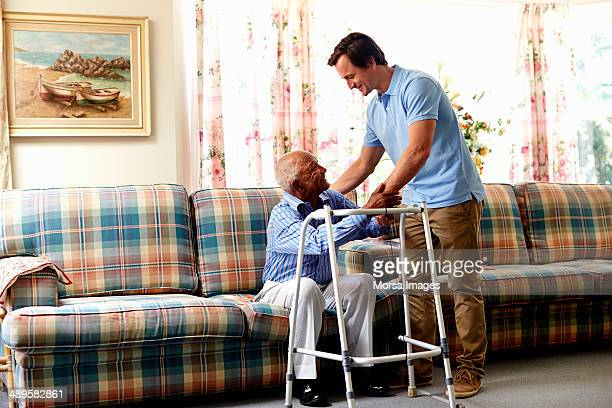 caretaker helping senior man with walker - janitorial services stock photos and pictures