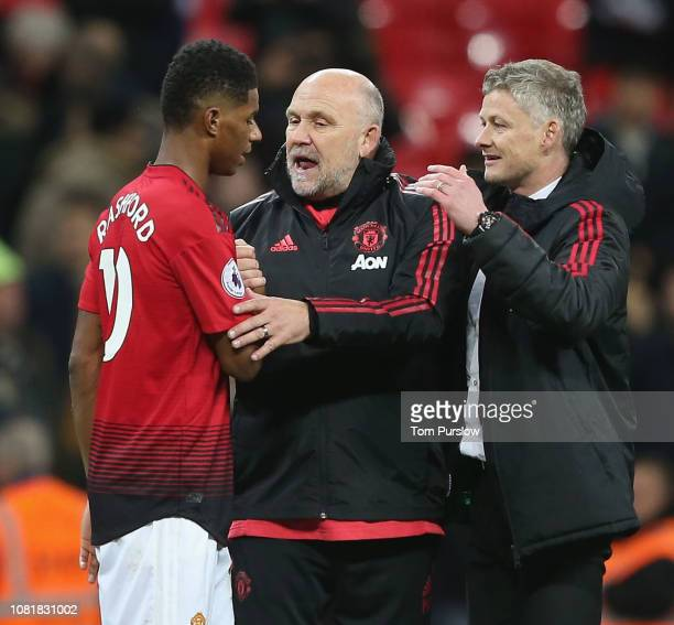 Caretaker Manager Ole Gunnar Solskjaer and Coach Mike Phelan of Manchester United congratulate Marcus Rashford after the Premier League match between...