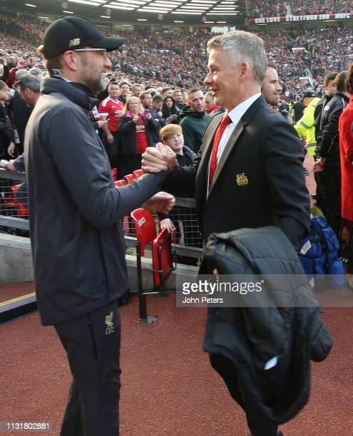 Caretaker Manager Ole Gunnar Solskjaer of Manchester United greets Manager Jurgen Klopp of Liverpool ahead of the Premier League match between...