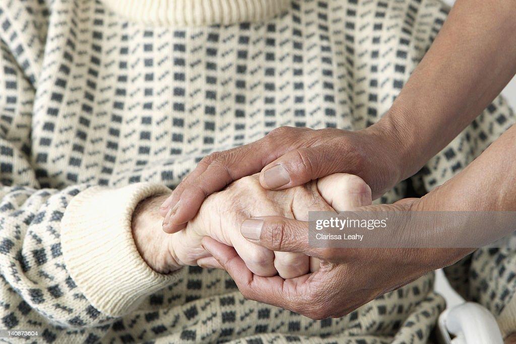 Caretaker patting older mans hand : Stock Photo