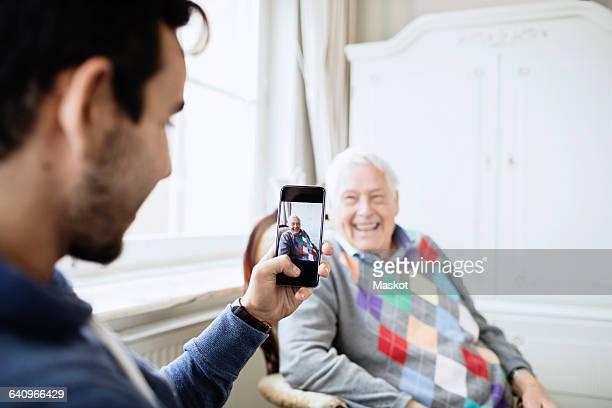 Caretaker photographing happy senior man through smart phone at nursing home