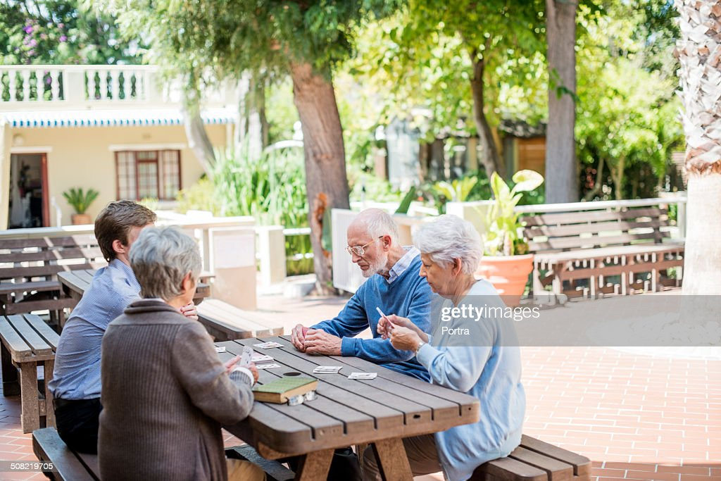 Caretaker playing cards with senior people : Stock Photo