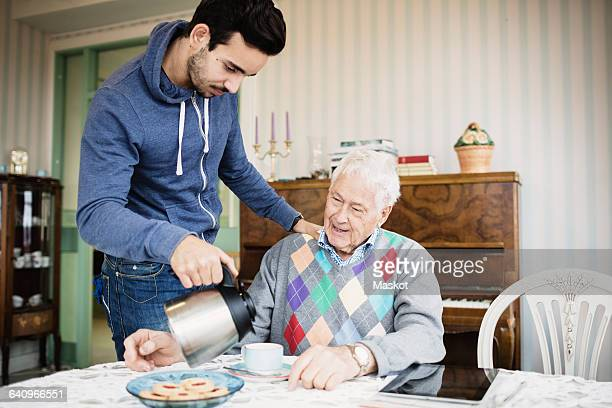Caretaker serving coffee to senior man at nursing home