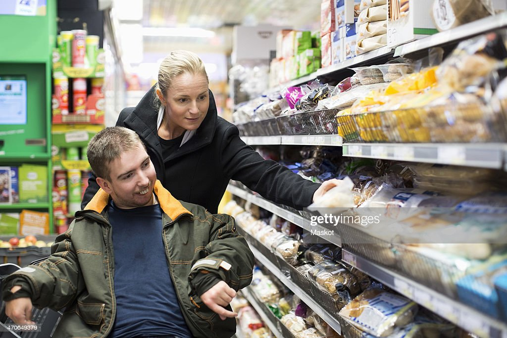 Caretaker shopping with disabled man on wheelchair in supermarket : Stock Photo
