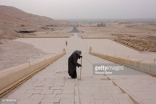 A caretaker sweeps dusty steps at the otherwise deserted ancient Egyptian Temple of Hatshepsut near the Valley of the Kings Luxor Nile Valley Egypt...