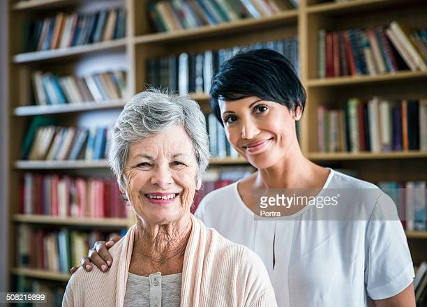 Caretaker with arm around senior woman in library