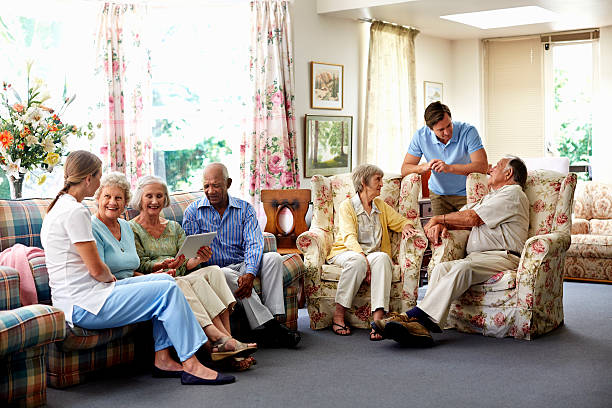 caretaker with retired people in nursing home - care home stock pictures, royalty-free photos & images