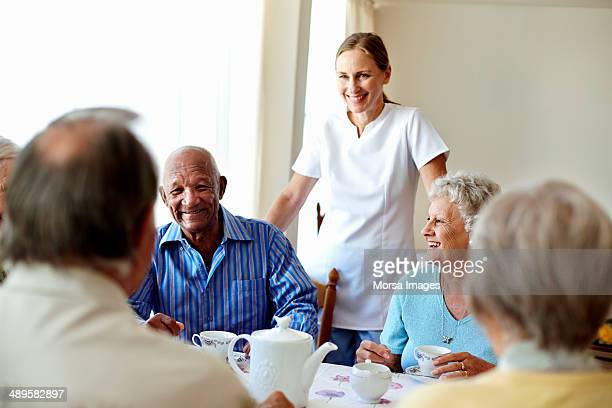 Caretaker with senior people enjoying coffee break