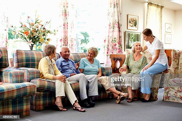 caretaker with senior people in nursing home - retirement community stock pictures, royalty-free photos & images