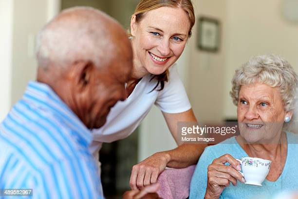 Caretaker with senior people in nursing home