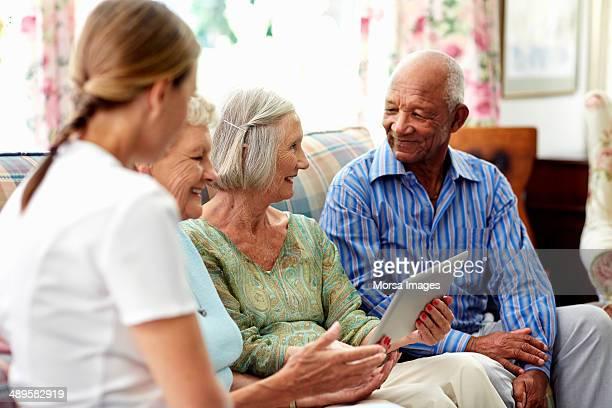Caretaker with senior people using digital tablet
