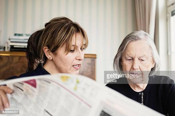 Caretaker with senior woman reading newspaper at nursing home