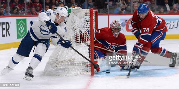 Carey Price and Alexei Emelin of the Montreal Canadiens defend the net against Ondrej Palat of the Tampa Bay Lightning in Game Four of the First...