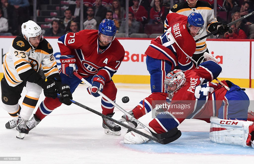 Carey Price #31 and Andrei Markov #79 of the Montreal Canadiens fight for the puck with Chris Kelly #23 of the Boston Bruins in the NHL game at the Bell Centre on October 16, 2014 in Montreal, Quebec, Canada.