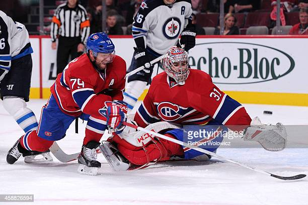Carey Price and Andrei Markov of the Montreal Canadiens watch the puck go wide on a shot by Evander Kane of the Winnipeg Jets during the NHL game at...