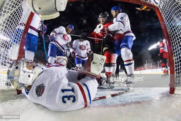 Carey Price of the Montreal Canadiens covers the puck in his crease as Shea Weber Jordie Benn and Tomas Plekanec look on against Ryan Dzingel of the...