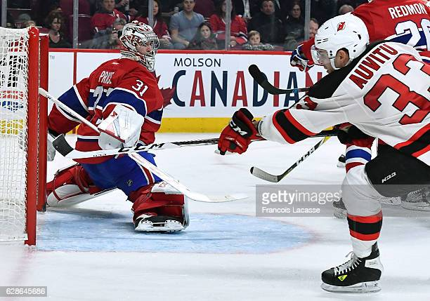 Carey Price of the Montreal Canadiens defends the goal against Yohann Auvitu of the New Jersey Devils in the NHL game at the Bell Centre on December...