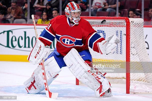 Carey Price of the Montreal Canadiens make a glove save on the puck during the warm up period prior to facing the Toronto Maple Leafs in their NHL...