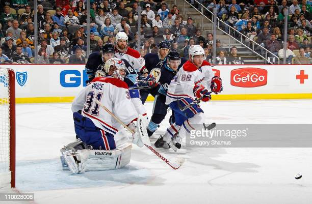 Carey Price of the Montreal Canadiens makes a save in front of Yannick Weber and Mark Letestu of the Pittsburgh Penguins on March 12, 2011 at Consol...