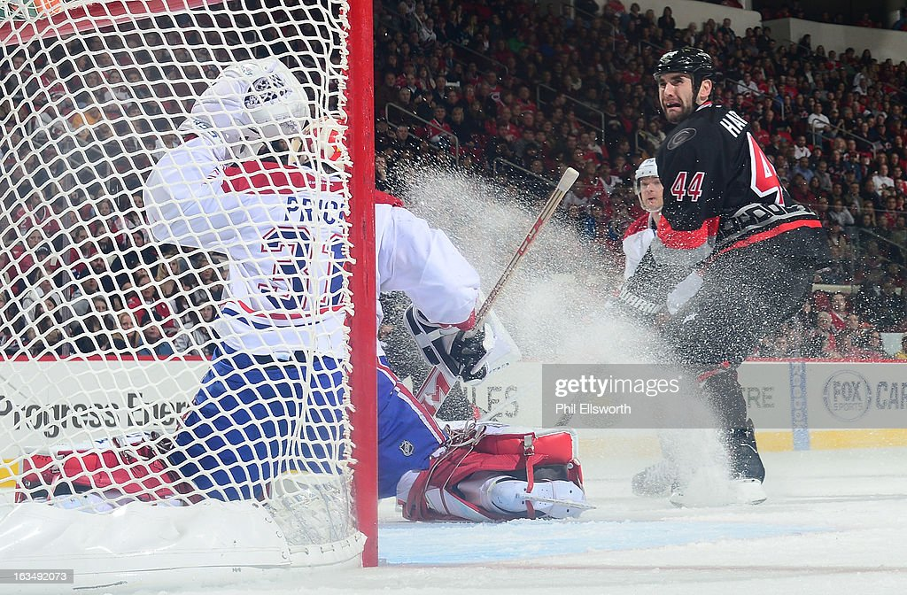 Carey Price #31 of the Montreal Canadiens makes a save with pressure up font from Jay Harrison #44 of the Carolina Hurricanes during an NHL game on March 7, 2013 at PNC Arena in Raleigh, North Carolina.