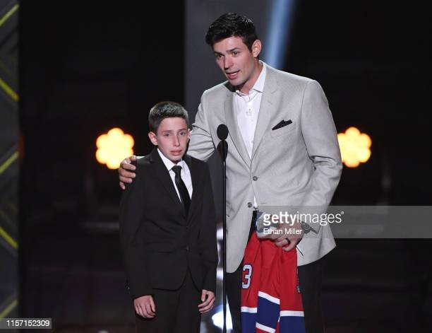 Carey Price of the Montreal Canadiens presents Anderson Whitehead with a jersey and a trip to the 2020 NHL AllStar Game during the 2019 NHL Awards at...