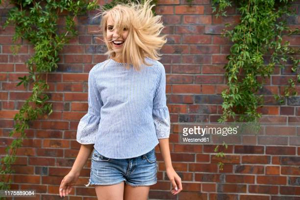 carferee young woman in motion at a brick wall - blue blouse stock pictures, royalty-free photos & images