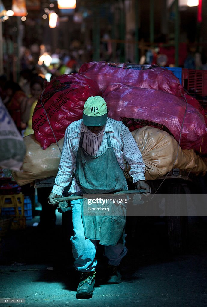 A cargador, or carrier, hauls a load of vegetables at the Terminal Market in Guatemala City, Guatemala, on Wednesday, Nov. 23, 2011. Foreign direct investment in Guatemala will stagnate this year at about $668 million, after rising 22 percent in 2010, according to the International Monetary Fund (IMF). Photographer: Victor J. Blue/Bloomberg via Getty Images
