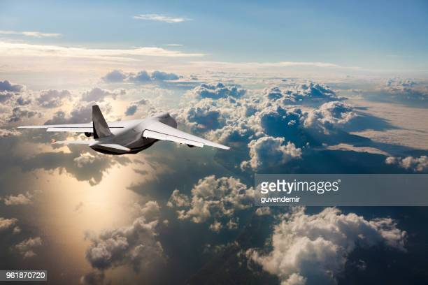 cargo airplane flying above the clouds at sunrise - cargo airplane stock photos and pictures