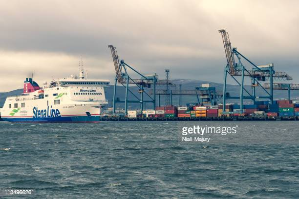 a cargo and passenger ferry passes the shipping container dock at belfast harbour - belfast stock pictures, royalty-free photos & images