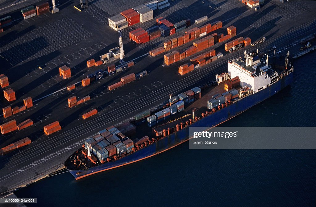 Cargo at quay loading freight container at port, aerial view : Stock Photo