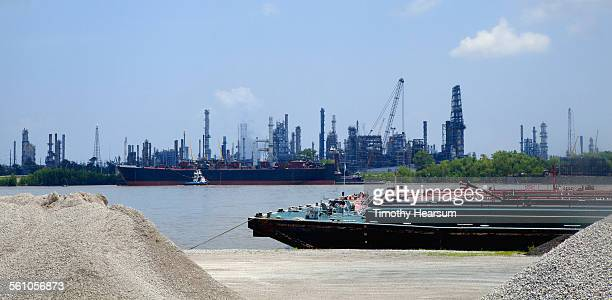 cargo barge on river; oil refineries beyond - timothy hearsum stock photos and pictures