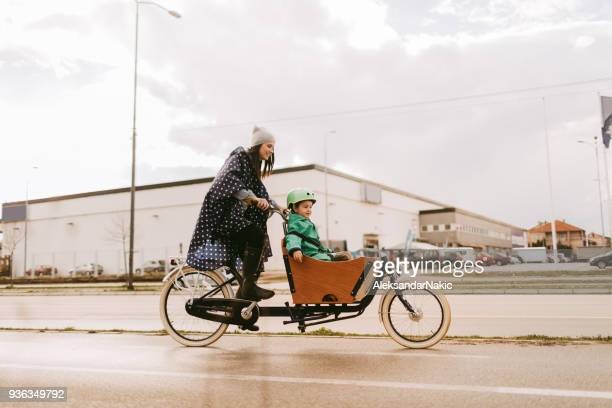 cargo bike ride on the rain - city life stock pictures, royalty-free photos & images